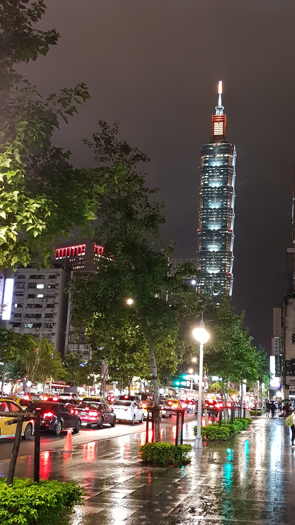 Taipei 101 towering in the distance, beautiful in the cold, wet night.