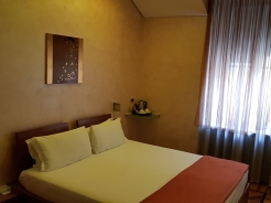 Hotel in Milan. Clean bed, warm coloured wall.