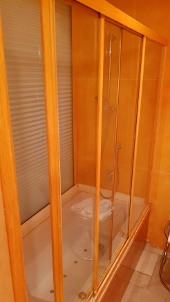 Sliding wooden and glass windows at the bath tub.