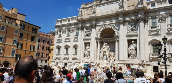 Hordes of tourists and peddlers at Fontana di Trevi. Rome, Italy.