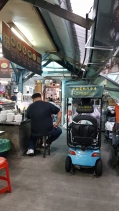 A lot of motorised vehicles weaving in and out within the market.