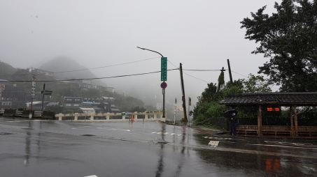 A distant mountain town, covered by the rain.