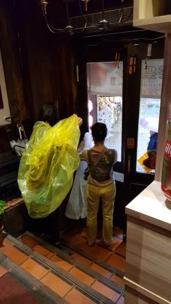 Yellow raincoat, cafe entrance.
