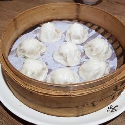 A bamboo basket of steaming Xiao Long Bao.