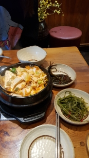 A bubbling hot pot of Korean tofu and kimchi soup.