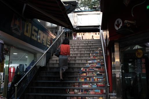 Woman climbing stairs. Namdaemun market. Seoul, Korea.