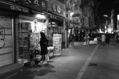 A lonely lady shopping. Black and white street photography of Isadong, Seoul, Korea.