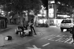 A pair of street musicians preparing for the night's performance. Black and white street photography of Isadong, Seoul, Korea.