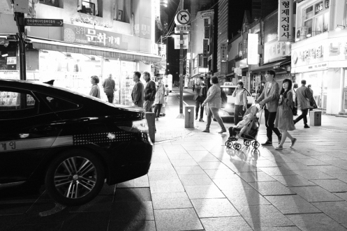 A man and wife pushing their child in a pram on the street. Black and white street photography of Isadong, Seoul, Korea.