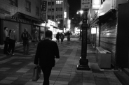 Tired man in a business suit, walking home. Black and white street photography of Isadong, Seoul, Korea.