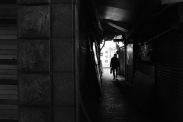 Man walking through a dark alley. Black and white street photography of Isadong, Seoul, Korea.