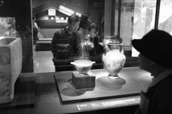 Visitors admiring ancient Etruscan artifact in National Museum of Korea.