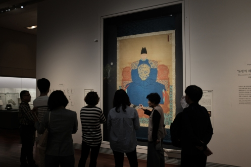 Museum visitors admiring a painting of an ancient Korean official in National Museum of Korea