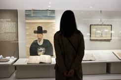 Silhouette of a woman admiring an old Korean painting in National Museum of Korea.