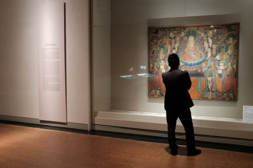Back of a man standing infront of a religious painting displayed in National Museum of Korea.