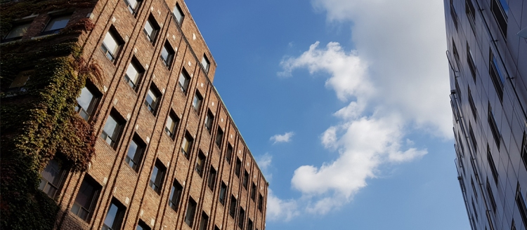 Beautiful brick building against a clear blue sky with fluffy white clouds.