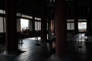 A group of visitors staring into the throne room from the front door of the throne room in Gyeongbokgung Palace. Seoul, Korea.