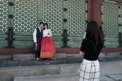 A young couple in traditional Korean attire having their picture taken by a passerby inGyeongbokgung Palace. Seoul, Korea.