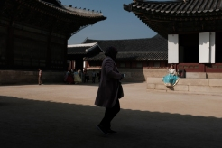 Passerby staring at a young lady in hanbok in Gyeongbokgung Palace. Seoul, Korea.