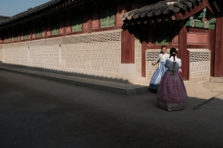 Two young ladies in Korean hanbok taking pictures of themselves in Gyeongbokgung Palace. Seoul, Korea.