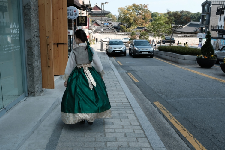 Young lady wearing traditional Korean hanbok walking down modern day Seoul, Korea.